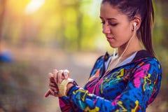 Fille Smartwatch de port pulsant de sport et écouteurs sans fil photos libres de droits