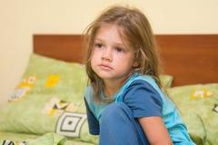Fille somnolente triste de cinq ans réveillant se reposer sur le lit Photographie stock libre de droits