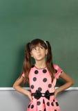 Fille songeuse d'enfant près de tableau noir vide d'école Images stock
