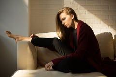 Fille songeuse dans un manteau rouge se reposant sur l'intérieur de sofa au soleil Image libre de droits