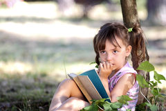Fille songeuse lisant un livre Photos stock
