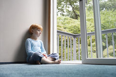 Fille songeuse regardant par le balcon photographie stock
