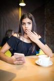 Fille soucieuse de portrait de plan rapproché la jeune regardant le téléphone voyant la mauvaise nouvelle ou les photos avec émot images libres de droits