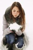 Fille soufflant sur la neige photo stock