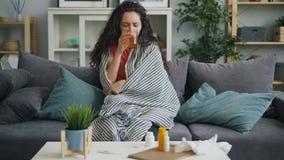 Fille souffrante prenant la médecine buvant du verre toussant alors dans seule la maison clips vidéos