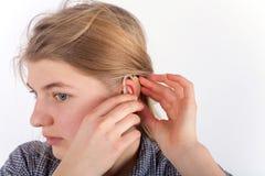 Fille sourde insérant la prothèse auditive Image stock