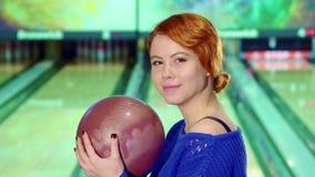 Fille souriant avec la boule de bowling dans des ses mains banque de vidéos