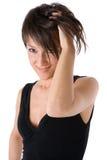 Fille souriant avec la main entre le cheveu Photographie stock libre de droits