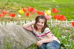 Fille souriant devant des fleurs Image stock