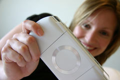 Fille souriant et jouant la console tenue dans la main de jeu images stock