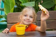 Fille souriant et mangeant un sandwich avec le thé pour le petit déjeuner Photos libres de droits