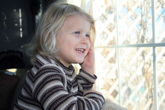 Fille souriant par l'hublot. Images libres de droits