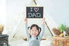 Fille souriant tout en tenant le tableau noir Image stock