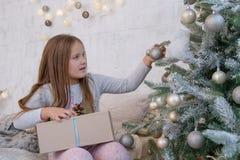 Fille sous l'arbre de Noël avec la boule Image stock