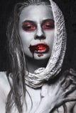 Fille sous la forme de zombis, cadavre de Halloween avec le sang sur ses lèvres Image pour un film d'horreur Photos stock