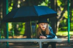 Fille sous un parapluie noir dans un chapeau marchant pendant le jour d'été de parc Photo stock