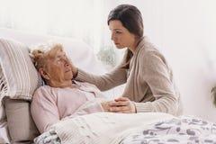 Fille soutenant la mère malade se situant dans le lit d'hôpital image stock