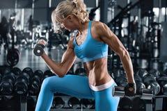 Fille sportive établissant dans le gymnase Femme de forme physique faisant l'exercice photos stock