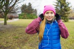 Fille sportive adolescente écoutant la musique extérieure Images stock