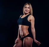 Fille sportive avec de grands muscles dans les vêtements de sport noirs Jeune femme sportive bronzée Un grand corps féminin de sp Image libre de droits