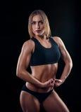 Fille sportive avec de grands muscles dans les vêtements de sport noirs Jeune femme sportive bronzée Un grand corps féminin de sp Photos libres de droits