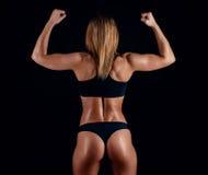 Fille sportive avec de grands muscles dans les vêtements de sport noirs Jeune femme sportive bronzée Un grand corps féminin de sp Image stock