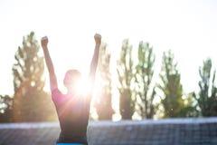 Fille sportive de coureur faisant des gestes le symbole de victoire contre le coucher du soleil L'espace pour le texte photographie stock
