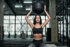 Fille sportive et attirante posant avec une boule lourde pour une forme physique Photos libres de droits