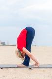 Fille sportive faisant le Headstand soutenu, asana Uttanasana de yoga sur le fond de côte photographie stock