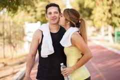 Fille sportive mignonne embrassant son ami Photographie stock
