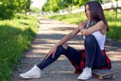 Fille sportive s'asseyant sur la planche ? roulettes Dehors, mode de vie urbain photo stock