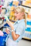 Fille stupéfaite au marché choisissant des cosmétiques Photographie stock libre de droits