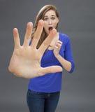 Fille stupéfaite avec la grande main en avant pour le concept de la précaution Photographie stock libre de droits