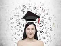 Fille stupéfaite avec le chapeau d'obtention du diplôme et le sketche faisants de la lévitation d'éducation Image stock