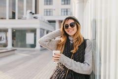 Fille stupéfiante dans des lunettes de soleil élégantes avec les cheveux blonds appréciant le café et pose extérieure avec la mai photo libre de droits