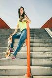 Fille sur des escaliers avec la planche à roulettes Photo stock