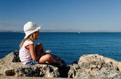 Fille sur des roches de bord de la mer Photographie stock