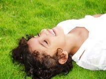 Fille sur l'herbe avec des yeux fermés Image libre de droits