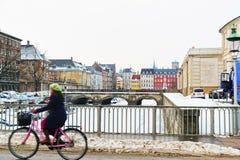 Fille sur la bicyclette passant par le pont en hiver Copenhague Image libre de droits