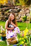 Fille sur la chasse à oeuf de pâques avec le lapin de Pâques vivant Photos stock