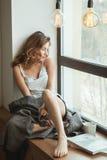 Fille sur la fenêtre avec une tasse de café et de magazine Photos libres de droits