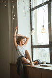 Fille sur la fenêtre avec une tasse de café et de magazine Image stock