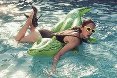 Fille sur la mer avec le matelas gonflable bain de fille sur le crocodile dans la piscine photographie stock libre de droits