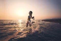Fille sur la plage au temps de coucher du soleil Image libre de droits