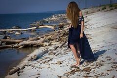 Fille sur la plage aux rondins Photographie stock