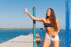 Fille sur la plage avec les cheveux humides, le beau chiffre et la peau propre contre la mer par temps ensoleillé Images libres de droits