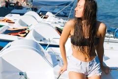 Fille sur la plage avec les cheveux humides, le beau chiffre et la peau propre contre la mer par temps ensoleillé Photo stock