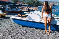 Fille sur la plage avec les cheveux humides, le beau chiffre et la peau propre contre la mer par temps ensoleillé Photos stock
