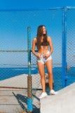 Fille sur la plage avec les cheveux humides, le beau chiffre et la peau propre contre la mer par temps ensoleillé Images stock