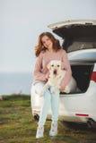 Fille sur la plage avec un Labrador blanc et une voiture blanche Image stock